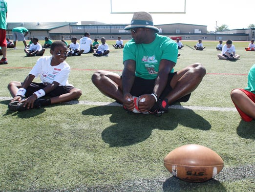 Former Neptune sports star and current NFL player for the Philadelphia Eagles Vinny Curry conducted youth football camp at Neptune High School.  Here Curry (center) warms up with a few of the youngest athletes during the camp.   On Saturday June 28,2014 Photo: Mark R. Sullivan/Staff Photographer