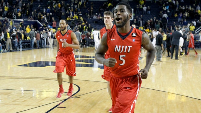 Damon Lynn of the New Jersey Institute of Technology runs off the court with teammates while celebrating a 72-70 win over Michigan at the Crisler Center on Dec. 6, 2014 in Ann Arbor.