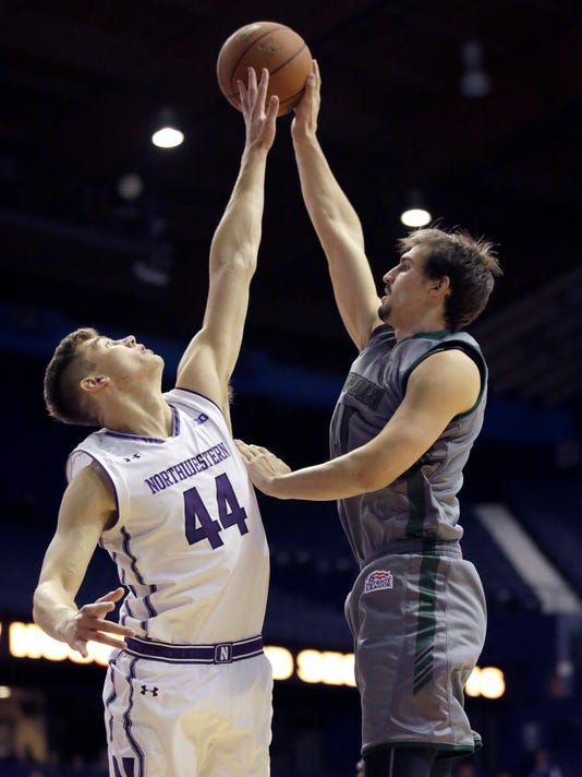 Northwestern forward Gavin Skelly, left, blocks a shot by Loyola (Md.) forward Ian Langendoefer during the first half of an NCAA college basketball game Friday, Nov. 10, 2017, in Rosemont, Ill. (AP Photo/Nam Y. Huh)