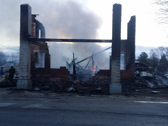 Flames continued to flicker Wednesday morning, hours