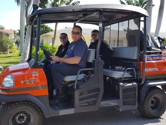 Three Greater Naples Fire Department paramedics/firefighters ride through Isles to provide any medical assistance that might be needed during the 30th annual All-Island Yard Sale on Capri.