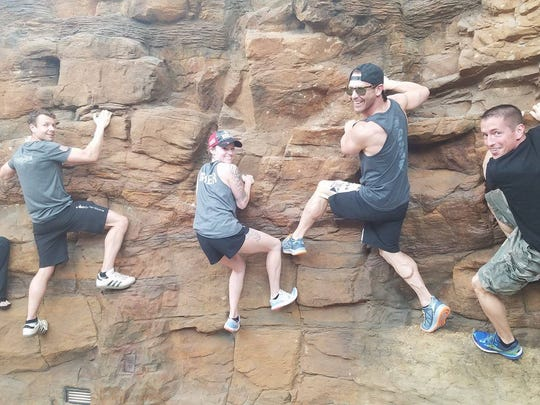 Team Little Giants members Jodie Fleming , Dustin Livengood, Liz Schlagel, Kevin Donoghue and Corey Raymo scale a wall.