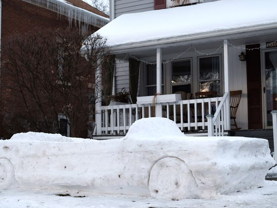 A model of a 1965 Ford Mustang made of snow sits in