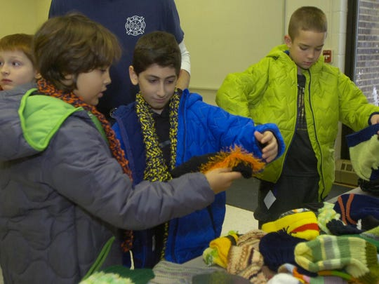 Lanigan fourth-graders John Richardson (left) and Sameer Daddoo check out some hats.