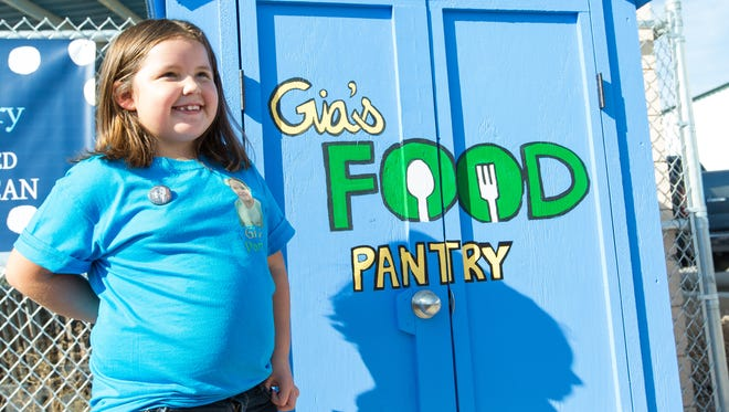 Gia Garcia, 7, stands next her creation, Gia's Food Pantry, a community food pantry located in front of the Community of Hope, on Saturday, October 22, 2016.