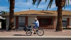 Postal worker Jeff Frehner delivers mail by bike on Dec. 3 in Sun City, Ariz.
