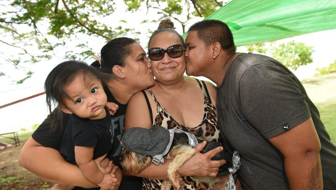 Bobbie Talavera, center, receives a kiss from nieces Samantha Toves, left, and Katherine Hermal on Mother's Day at Gov. Joseph Flores Memorial Park on May 14, 2017.