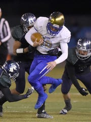 Reed's Camerson Emerson is tackled by Damonte defenders as he runs with the ball on Nov. 17.