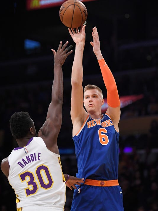 New York Knicks forward Kristaps Porzingis, right, of Latvia, shoots as Los Angeles Lakers forward Julius Randle defends during the first half on an NBA basketball game, Sunday, Jan. 21, 2018, in Los Angeles. (AP Photo/Mark J. Terrill)