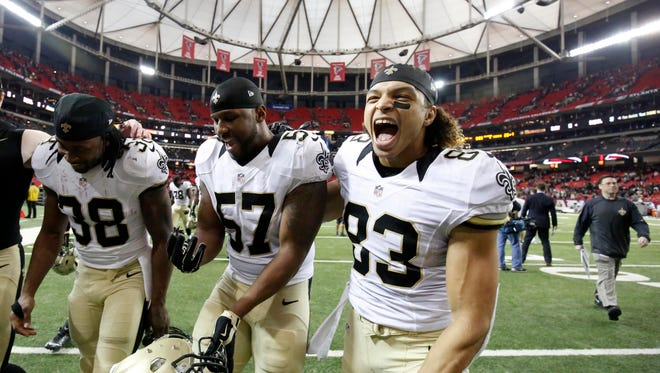 Jan 3, 2016; Atlanta, GA, USA; New Orleans Saints running back Travaris Cadet (38) and outside linebacker David Hawthorne (57) and wide receiver Willie Snead (83) celebrate as they walk off of the field following their win against the Atlanta Falcons at the Georgia Dome. The Saints won 20-17.