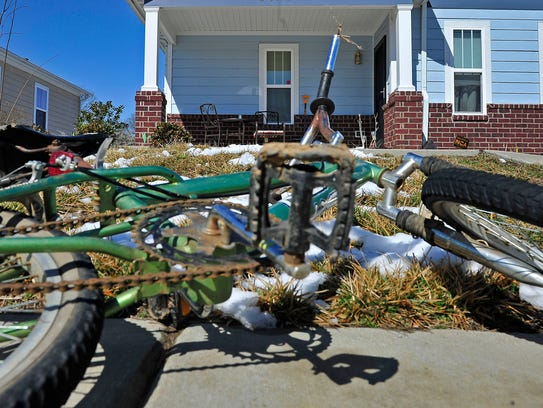 A bicycle lies on the sidewalk in front of the house