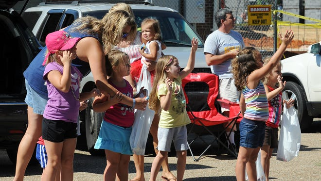 Children cheer and wave as floats pass during the Fourth of July parade in Sumrall.