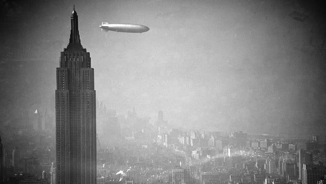 The German Zeppelin Hindenburg flies over Manhattan, passing the Empire State building, on May 6, 1937, a few hours before the disaster.
