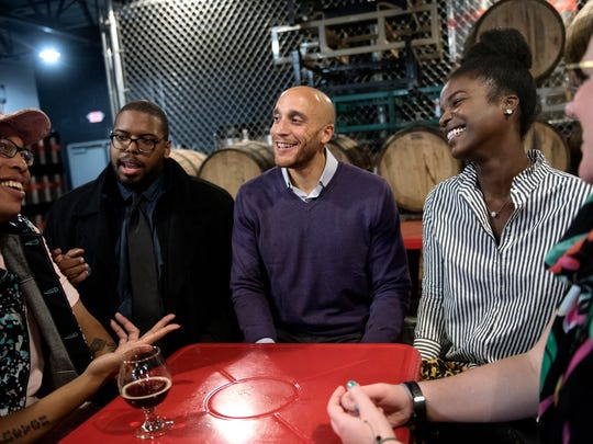 Fourth Ward Lansing City Council Member-elect Brian Jackson, center, and his wife, Arielle, right, celebrate Jackson's win with friends, from left, Jhevon Shaw, Derrell Slaughter and Jessica Fowler, far right, on Tuesday, Nov. 7, 2017, at the Lansing Brewing Company.