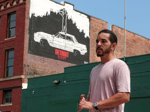 Detroit artist Nic Notion is seen by a mural he painted
