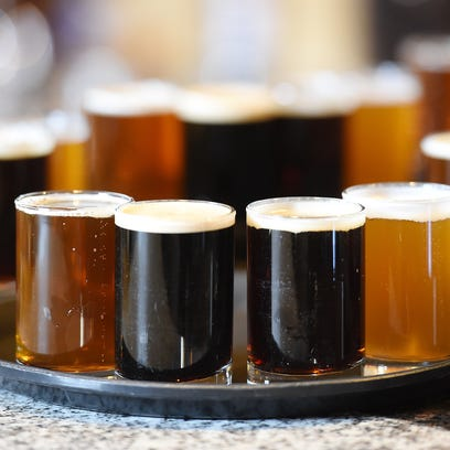 A beer flight is ready to serve to a tour group.