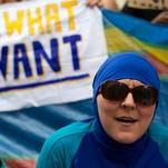 """A woman wearing a burkini joins a protest outside the French Embassy in London on Aug. 25, 2016, during a """"Wear what you want beach party"""" to demonstrate against the ban on burkinis on French beaches."""