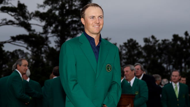 Jordan Spieth poses with his green jacket after winning the Masters golf tournament Sunday in Augusta, Georgia.