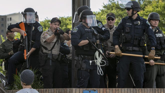 Police stand near protesters at Austin Police Department headquarters during a May 30 protest against police brutality. Eleven officers have been disciplined over the protests, according to city officials.