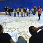 Oak Grove Lower Elementary second-grade students look at a floor map of Asia provided by the National Geographic Association on Wednesday in the Oak Grove Lower Elementary multipurpose building.