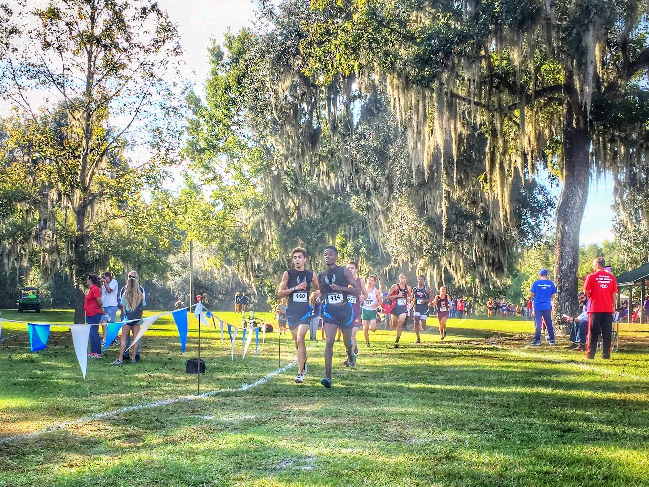 Rickard seniors Evan Garrison (left) and Solomon Stevens race into the final mile of Saturday's Region 1-2A meet at Alligator Lake. The pair qualified for the state meet and broke the school record in the process.