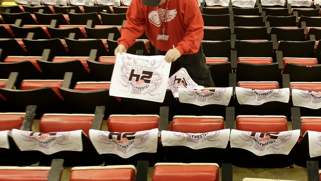 Red Wings fan Jim McCoy of Westland and a volunteer for the Red Wing For'Em Club places one of the 20,000 white towels on the seats in Joe Louis Arena before Game 6 Monday.