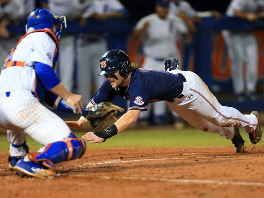 Auburn infielder Luke Jarvis slides safely into home