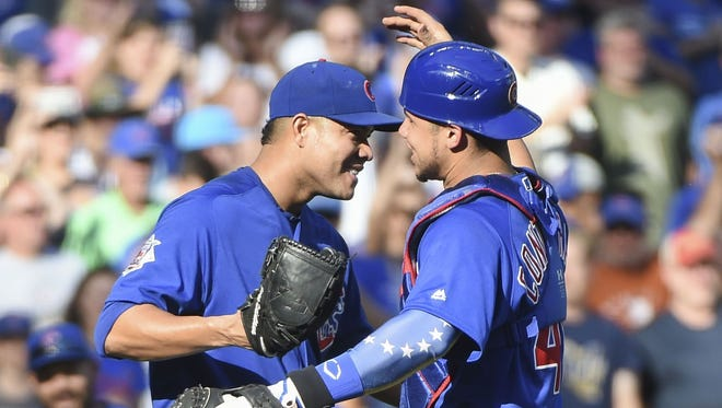 Cubs starting pitcher Jose Quintana gets a hug from catcher Willson Contreras after pitching a complete game three-hit shutout against the Brewers on Sunday at Miller Park.