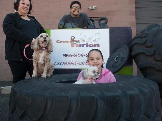 Stacy Aguilar, from left with her dog Bella, Gilbert Aguilar and Abby Aguilar with Dog Scout pose for a portrait at CrossFit Furion in West Berlin. Pet professionals provided dogs in attendance with a mini-spa treatment and photo shoot.