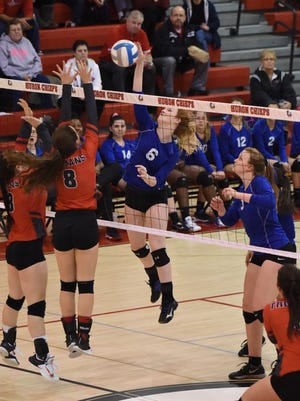 Smacking the ball over the outstretched arms of Clarenceville players is Ladywood's Mikayla Kuphal (6).