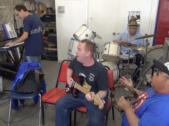 The Cretive Center band features Luis Navarrete on piano (far left), Robert Johnston on guitar (center), and Carlos Nunez (back) and Eddie Parez (front left) on percussion.