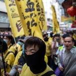 Protesters from the group Civic Action march in the streets of Yuen Long district, New Territories, in Hong Kong.