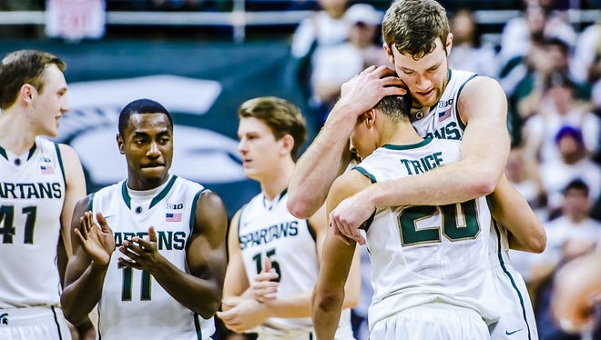 MSU's Matt Costello, top right, gives senior Travis Trice a hug as Trice checks out of his last home game. Trice scored 27 points and Costello had 13 points and four blocks in the Spartans' critical 72-66 win over Purdue.
