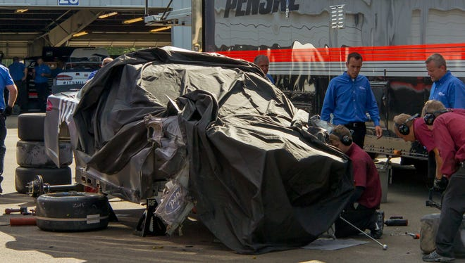The crew works to remove parts from Brad Keslowski's car after he hit the wall in Turn 1 Tuesday afternoon during testing at Waktins Glen International.
