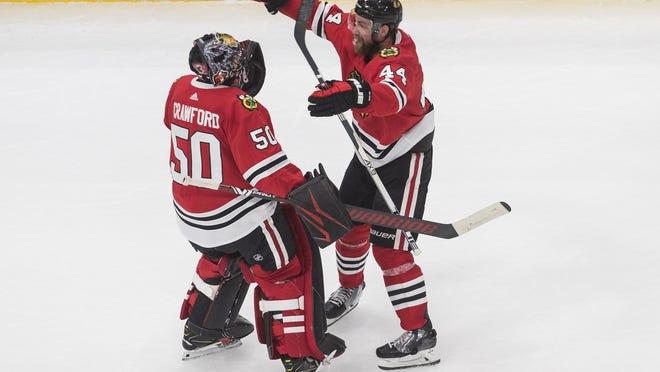 Chicago Blackhawks goalie Corey Crawford (50) and Calvin de Haan (44) celebrate their win over the Edmonton Oilers on Friday.