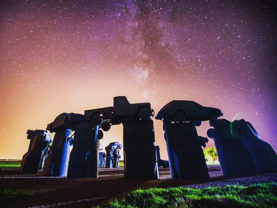 """""""Carhenge,"""" by Jim Reinders, is pictured at sunrise. The sculpture is located near Alliance, Neb."""