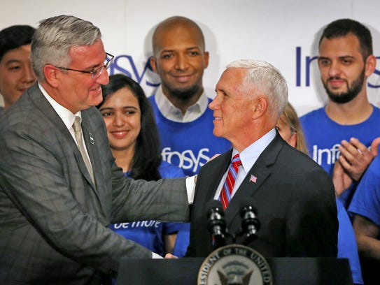 Governor Eric Holcomb, left, shakes hands with Vice