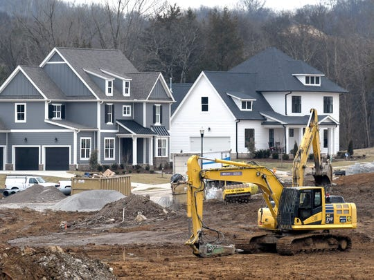 Workers move dirt for new homes in Enderly Pointe at Ladd Park in Franklin on Feb. 7, 2018.