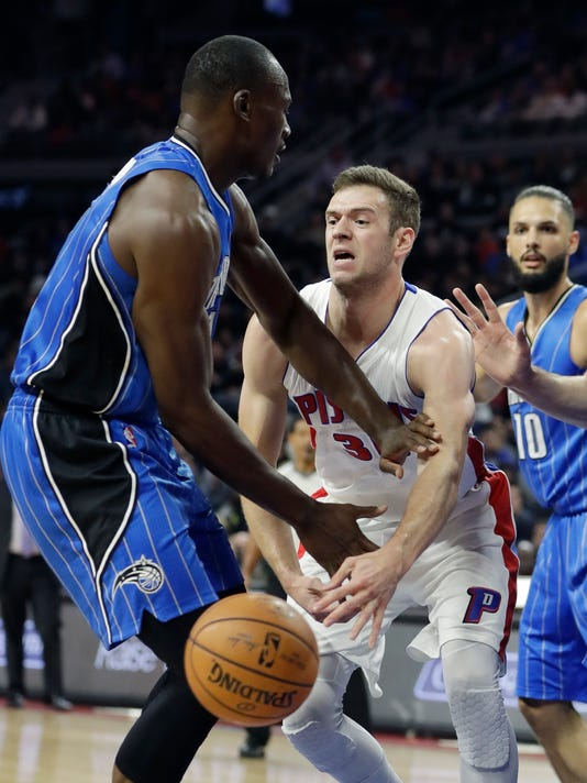 Detroit Pistons forward Jon Leuer (30) passes the ball around the defense of Orlando Magic center Bismack Biyombo (11) during the first half of an NBA basketball game, Friday, Oct. 28, 2016 in Auburn Hills, Mich. (AP Photo/Carlos Osorio)