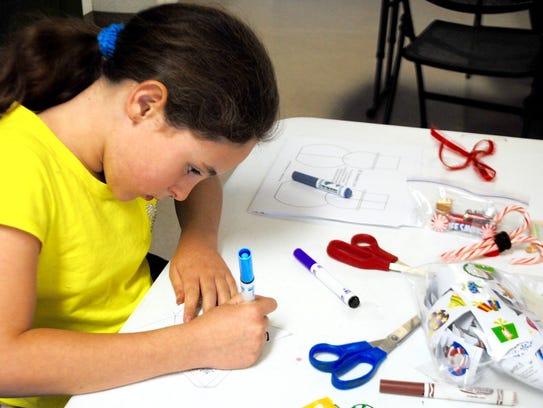 Kaitlin Fitzherbert, 9, uses multiple supplies in making