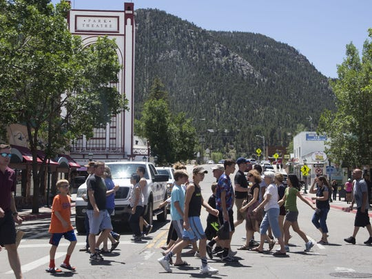 A large crowd of tourists cross Moraine and Elkhorn in Estes Park.