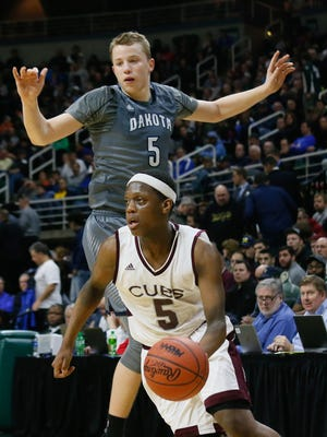 U-D Jesuit's Cassius Winston dribbles past Macomb Dakota's Thomas Kithier (5) during the 2016 MHSAA boys basketball Class A semifinals at the Breslin Center in East Lansing.