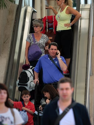 """Passengers travel down the escalator from the Sonny Bono Concourse at Palm Springs International Airport in March 2014.  PSP ranked at No. 5 for the Top 10 """"Worst Airports to Fly Out of Over the Holidays,"""" in a study compiled by SmartAsset, at site offering consumer tips."""