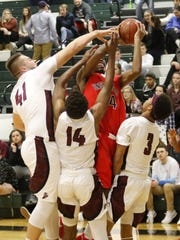 An example of Elmira's defensive work as Yachezqel Ogbonna of Binghamton tries to get a shot off while Dan Fedor (41), Daryl Savage (14) and Nahjor Mack defend during a 51-28 win Jan. 11 at Elmira High School.