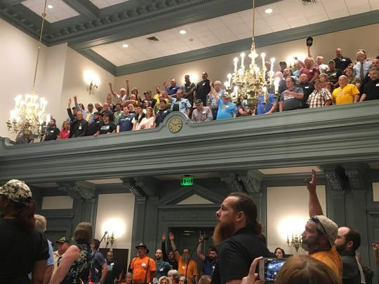 Opponents of a assault weapons ban stand in the chambers