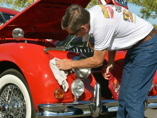 A proud owner shines his auto at a past  British Car