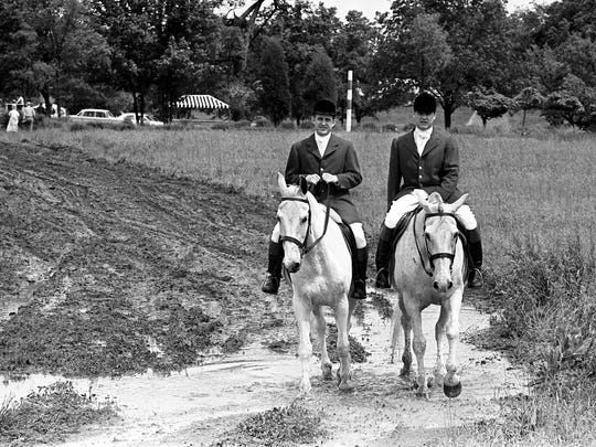 A couple of mounted outriders make their way from the stables to the Percy Warner Park course for the 26th annual running of the Iroquois Steeplechase on May 13, 1967.