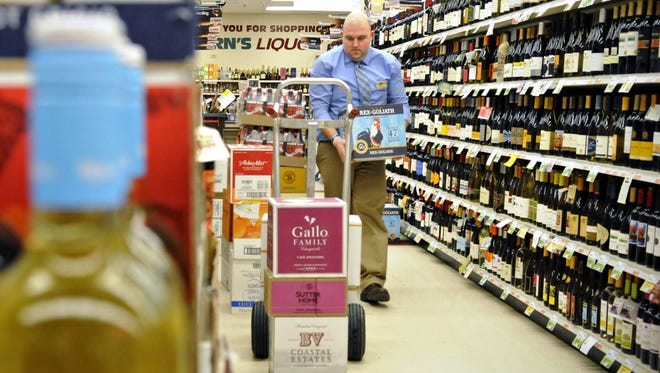 In this Dec. 19, 2014 file photo, Justin Riess, assistant manager at Coborn's Liquor in St. Cloud, stocks the shelves between customers.