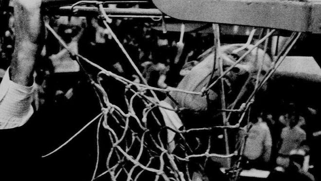 LSU head basketball coach Dale Brown takes a bite out of the net after the Tigers defeated Kentucky 59-57 to earn a trip to the 1986 Final Four.