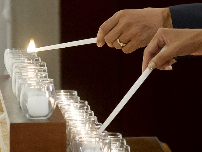 President Obama and first lady Michelle Obama light 26 candles, honoring the 26 students and teachers killed at Sandy Hook Elementary School in Newtown, Conn., in the map room of the White House in Washington, D.C. The Obamas also observed a moment of silence on the one-year anniversary of the shooting.
